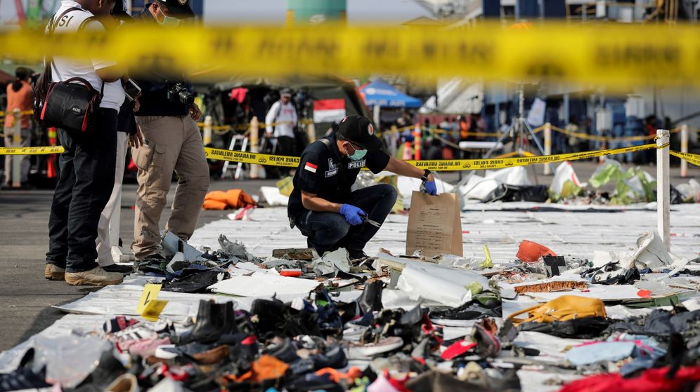 Foto: Un policía forense inspecciona restos del avión siniestrado en el mar de Java que se saldó con al muerte de 189 personas. (EFE)