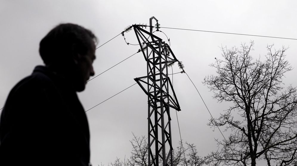 Foto: Un hombre pasa junto a una torreta con el tendido eléctrico caído por el temporal. (EFE)
