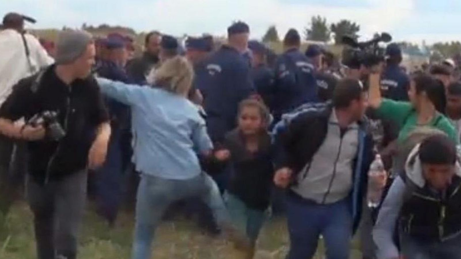 Foto: La reportera dando una patada a una niña. (Twitter)