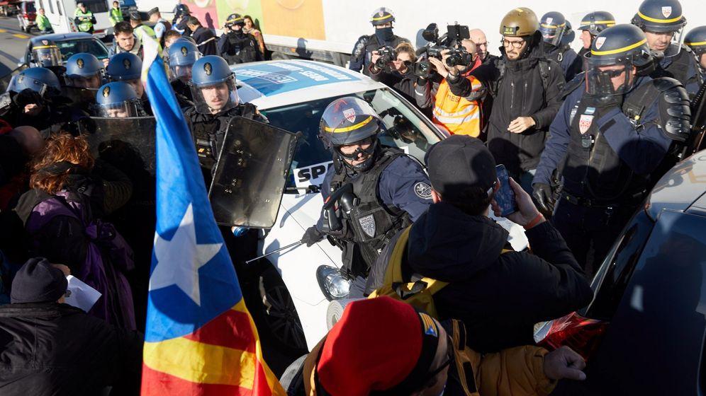 Foto: Gendarmes franceses tratan de desbloquear el corte de la autopista que enlaza España y Francia. (EFE)