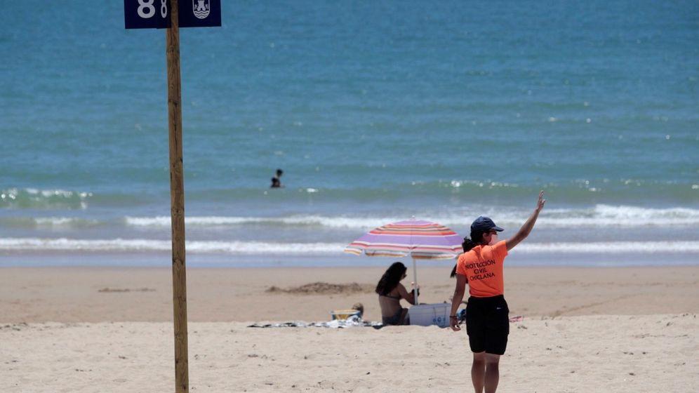 Foto: Personal de Protección Civil da indicaciones en una playa de Cádiz. (EFE)
