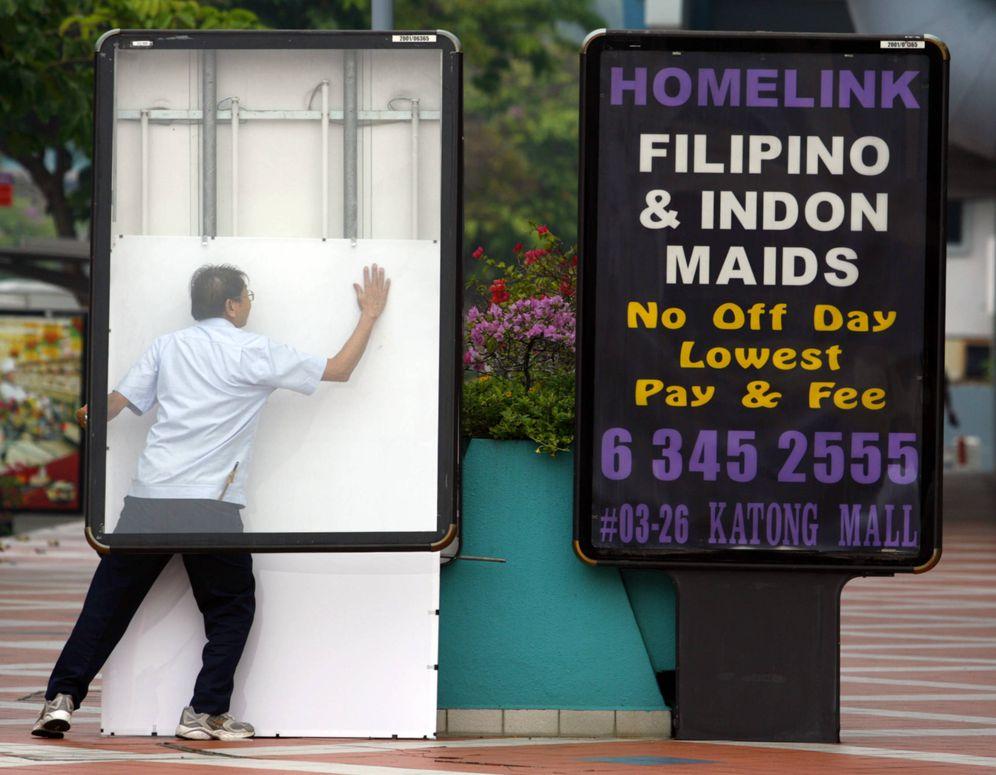 Foto: Un hombre coloca un panel tras el anuncio de una agencia de asistencias en Singapur, en 2006. (Reuters)