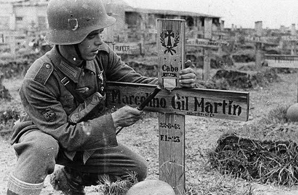 Foto: Un soldado español, con la ayuda de su machete, acaba de incrustar en la cruz de un compañero caído el símbolo de la unidad.