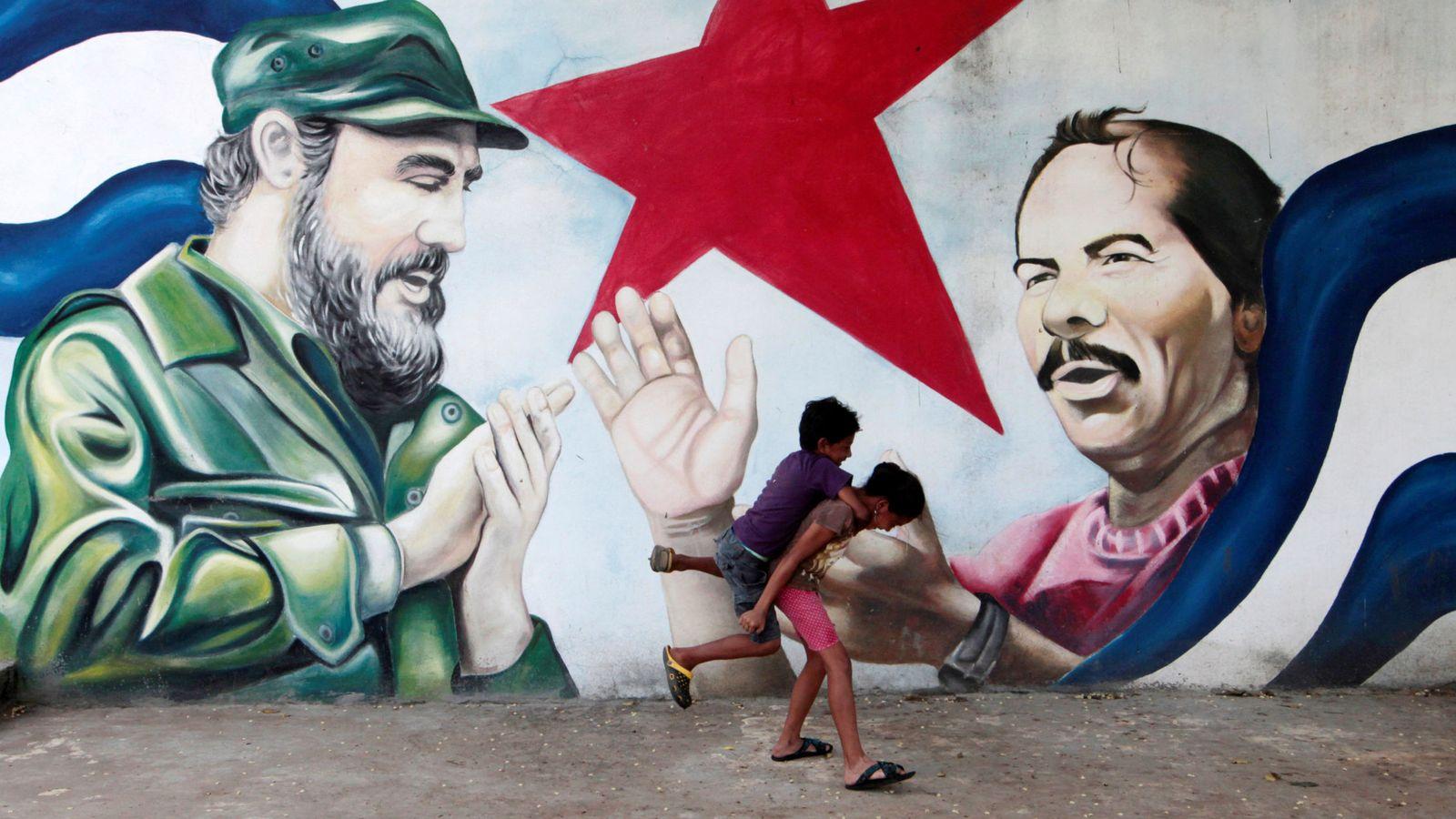 Foto: Dos niños corren frente a una mural de Fidel Castro y el presidente de Nicaragua Daniel Ortega. (Reuters)
