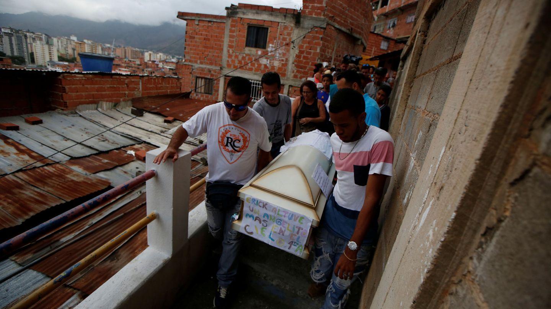 Varios familiares cargan con el féretro de Erick Altuve, un niño de 11 años que murió por problemas respiratorios. (Reuters)