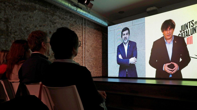 El 'expresident' Puigdemont (d) y Jordi Sànchez (i) en conversación por videoconferencia en la sede electoral de JxCAT. (EFE)