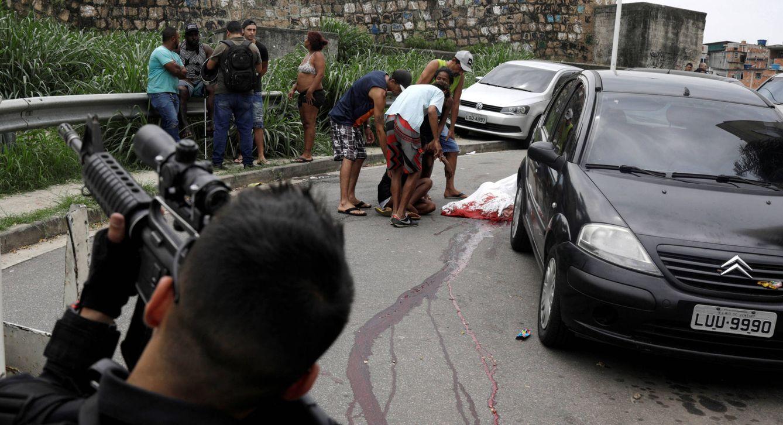 Foto: Familiares de una persona asesinada en la favela del Alemao junto al cadáver, en Río de Janeiro. (Reuters)