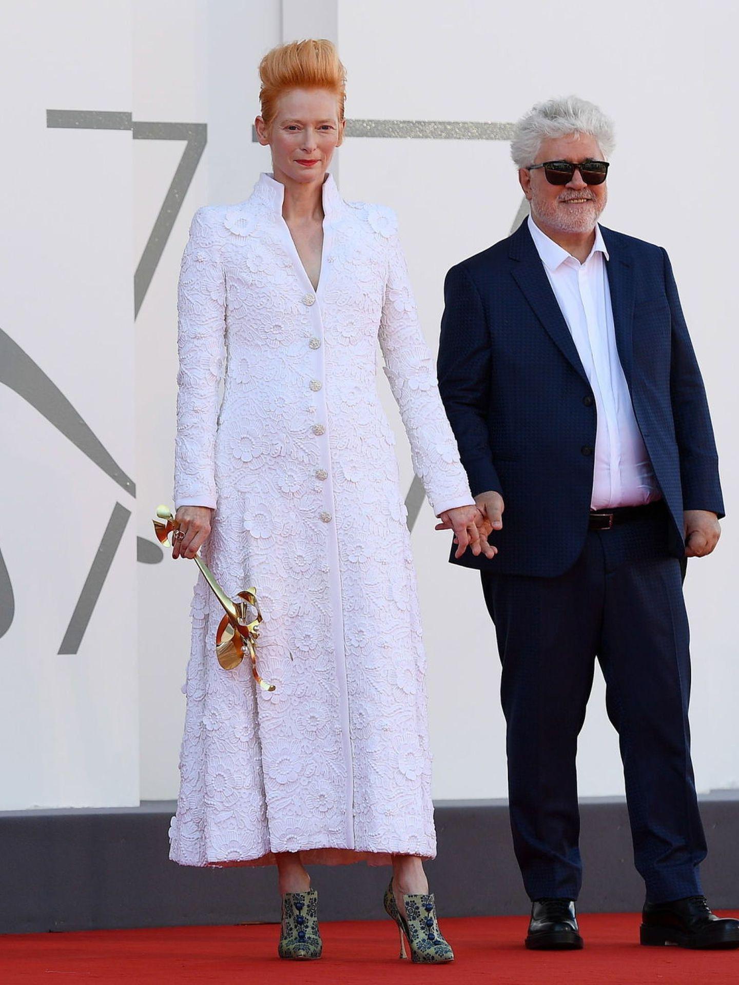 Pedro Almodóvar, con traje azul marino y camisa blanca, junto a Tilda Swinton, con vestido blanco de Chanel, en la presentación de 'The Human Voice'. (EFE)