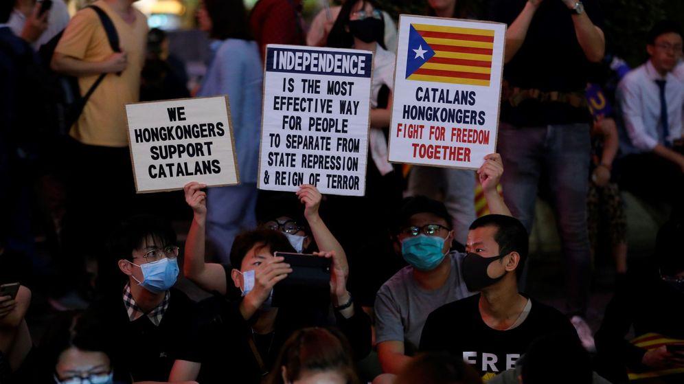 Foto: Unos hongkoneses con carteles en apoyo al independentismo catalán. (EFE)