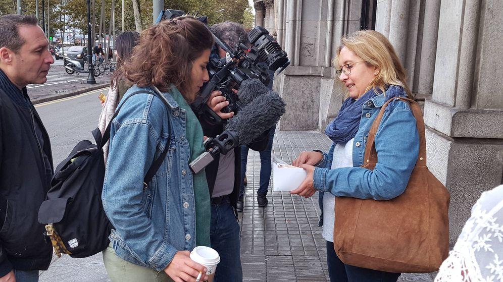 Foto: Una ciudadana muestra a los medios el efectivo retirado en una entidad de Barcelona. (A.P.)