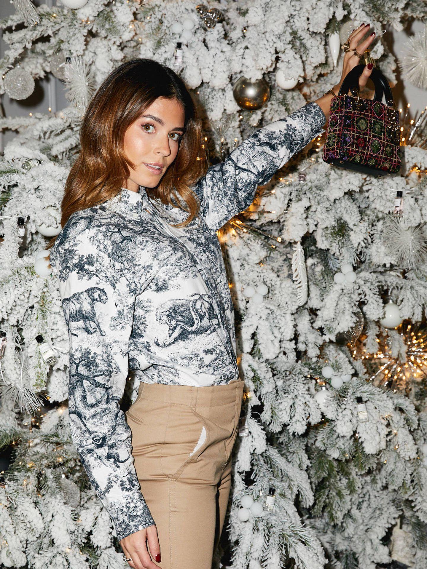 La modelo con camisa estampada, pantalón y bolso de Dior.