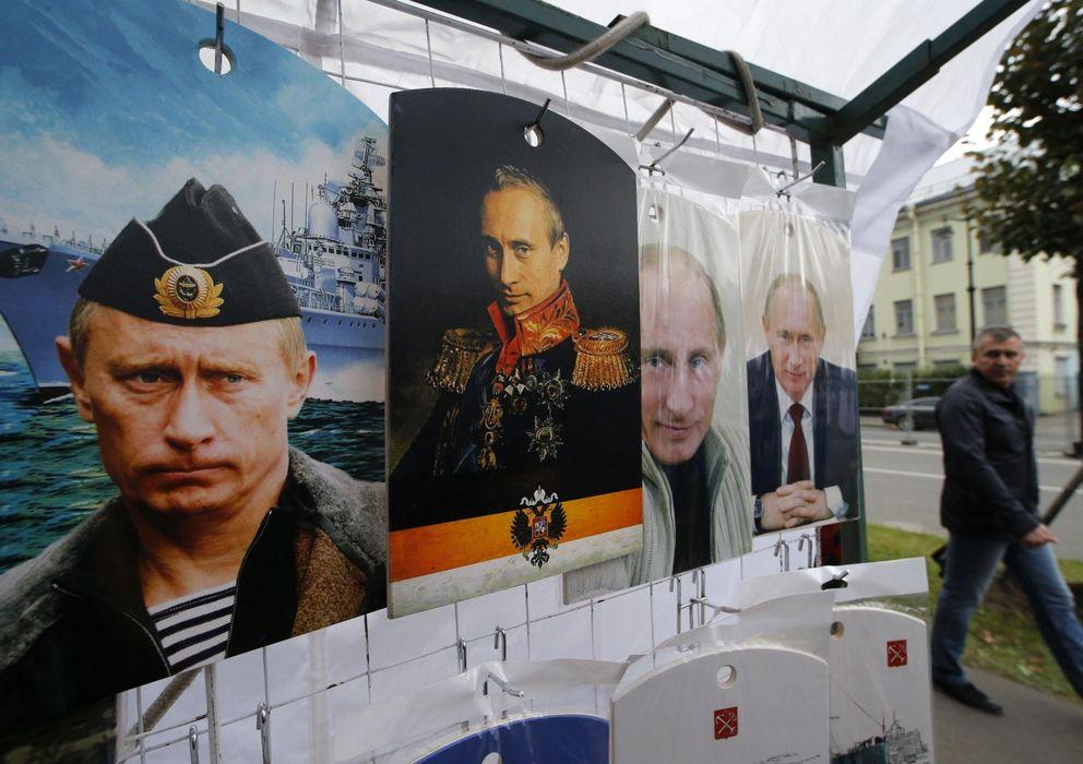 Foto: Un ruso camina ante una serie de pósters con imágenes del presidente ruso, Vladimir Putin, en San Petersburgo. (Reuters)