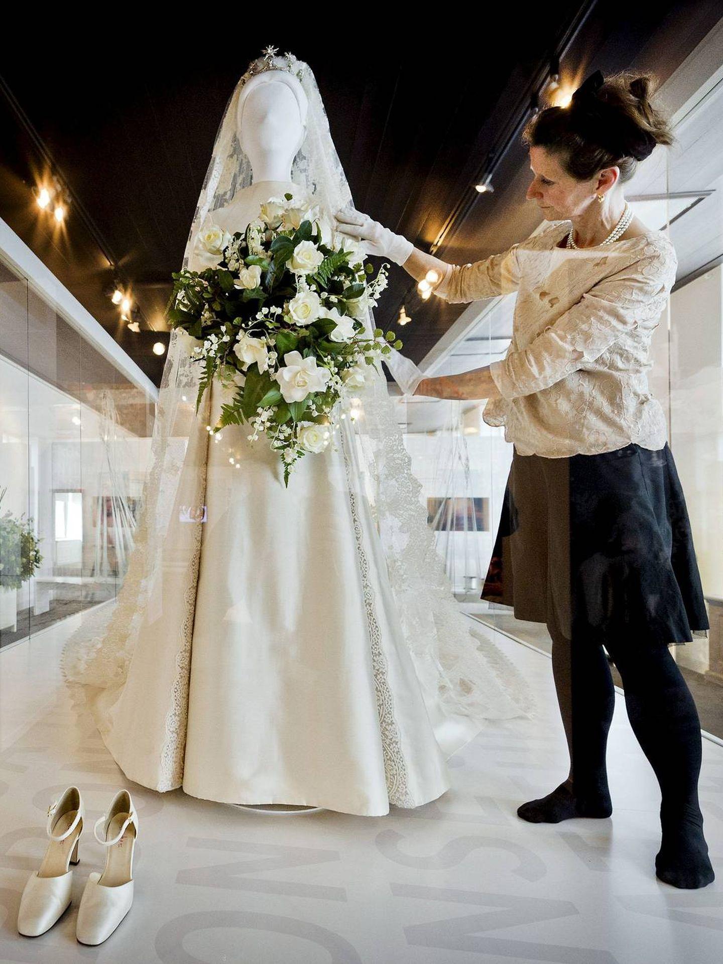 Una asistente coloca en un maniquí el vestido de novia de Máxima de Holanda. (EFE)