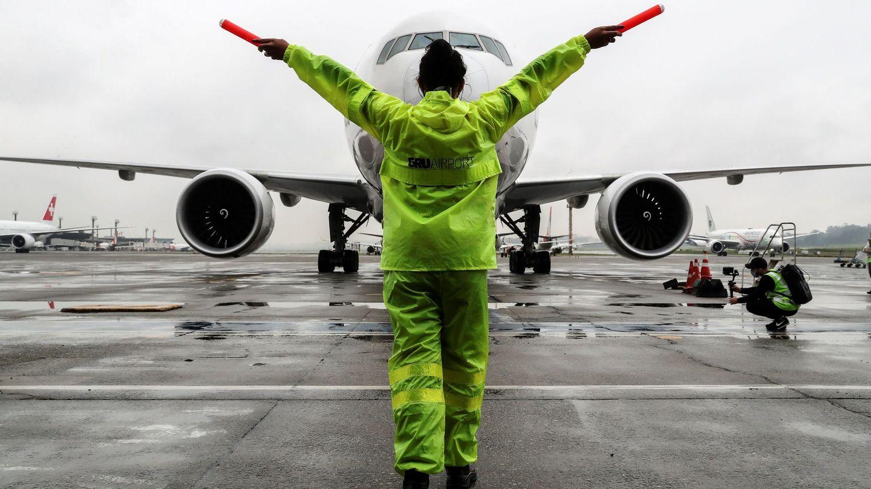 Una trabajadora guía el avión que contiene el cargamento de vacunas en el aeropuerto internacional de Guarulhos. (EFE)