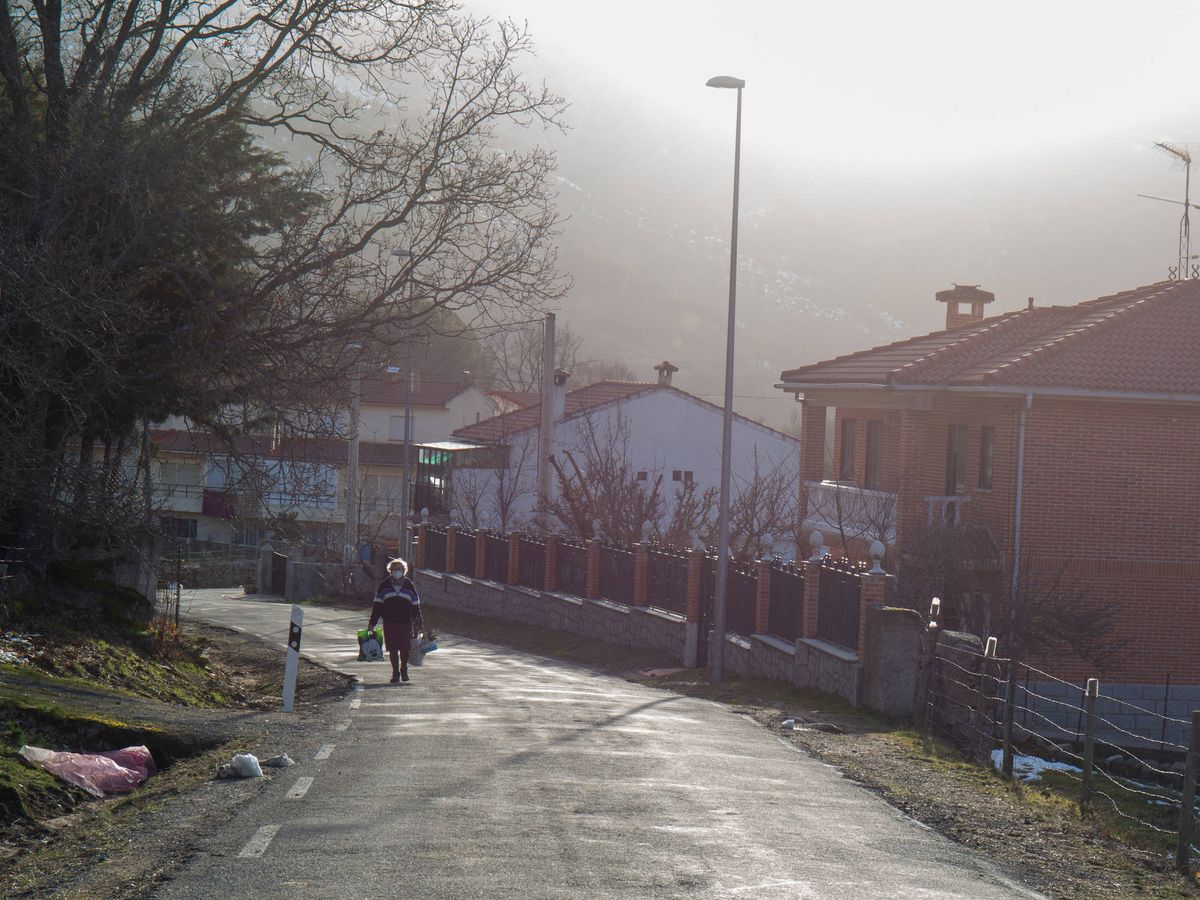 Foto: Una mujer camina por la carretera de Navacepedilla de Corneja. (David Brunat)