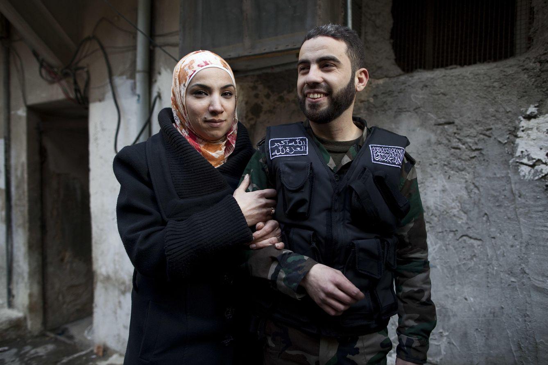 Foto: Yosef Abobaker en la puerta de su antigua casa en Alepo junto a su esposa Gada, el día de su boda (J.M. López).