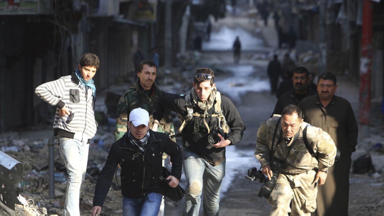 Bryn Karcha (c), de Canadá, y Toshifumi Fujimoto (d) de Japón corren en una calle de Alepo, Siria (Reuters).