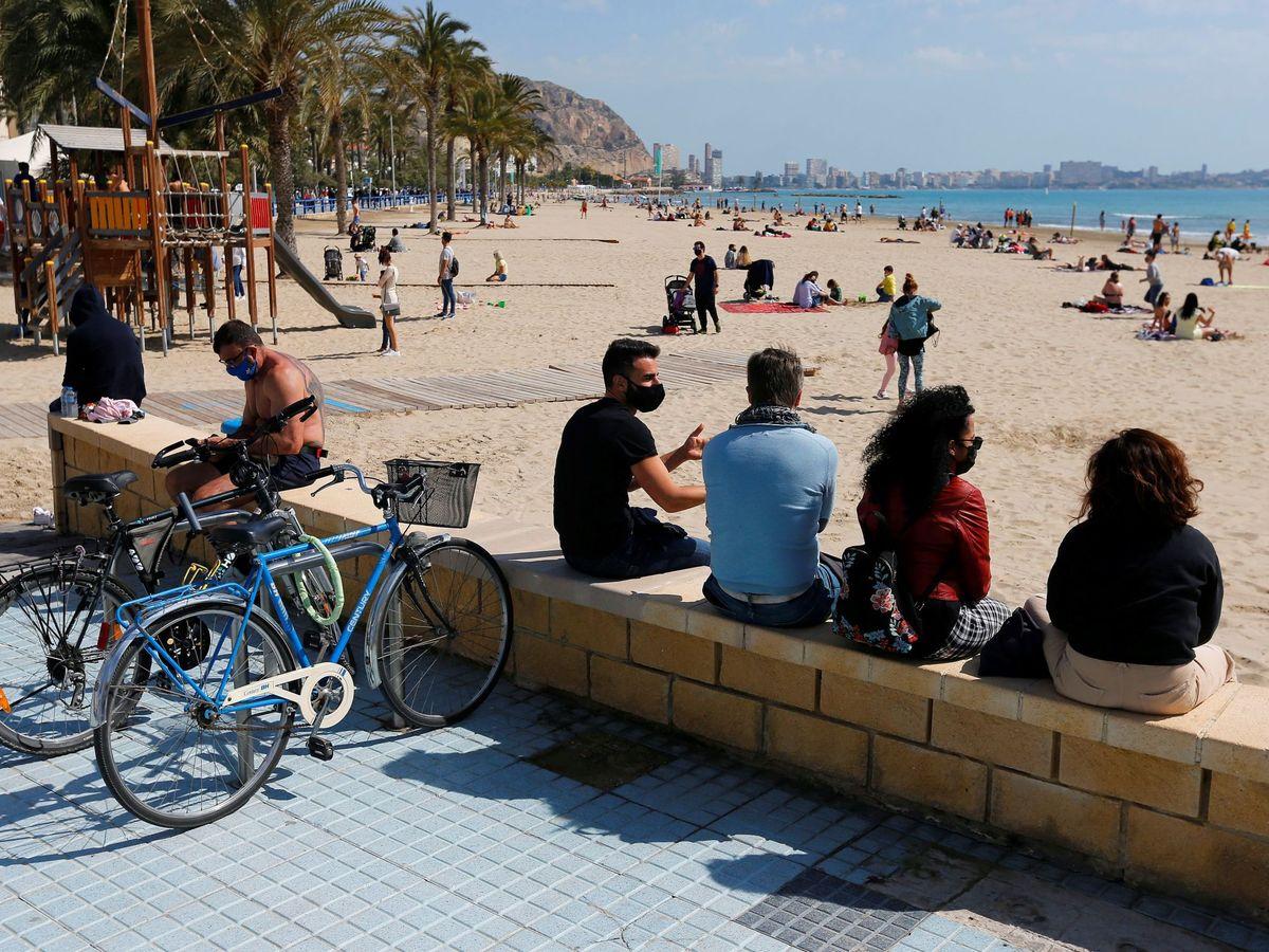 Foto: Turistas con mascarillas, en las playas alicantinas. (EFE)