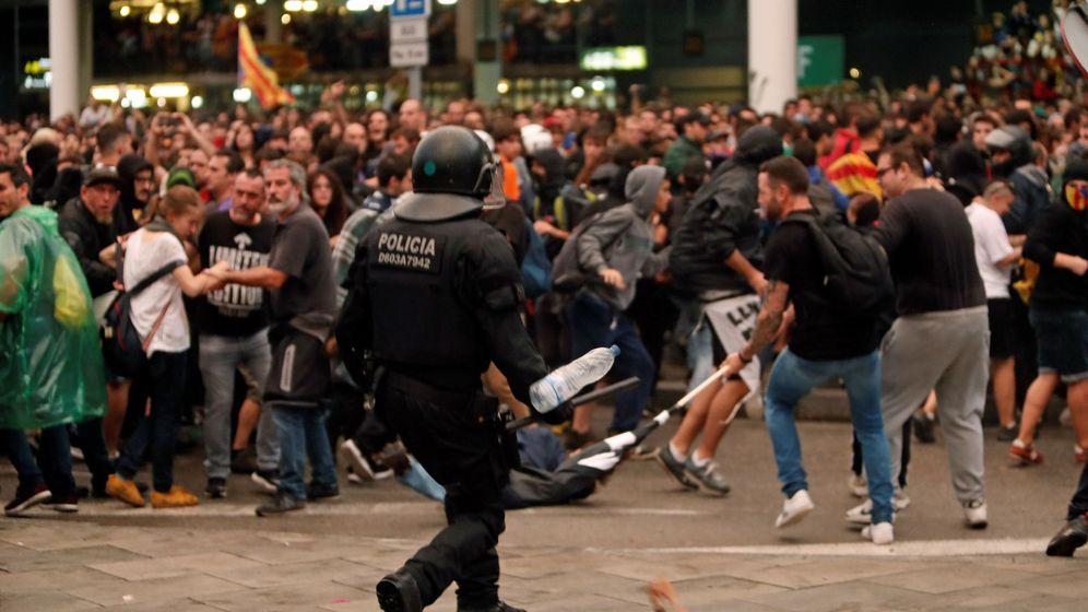 Foto: Un Mosso d'Esquadra ante cientos de manifestantes este lunes en el aeropuerto de El Prat. (EFE)