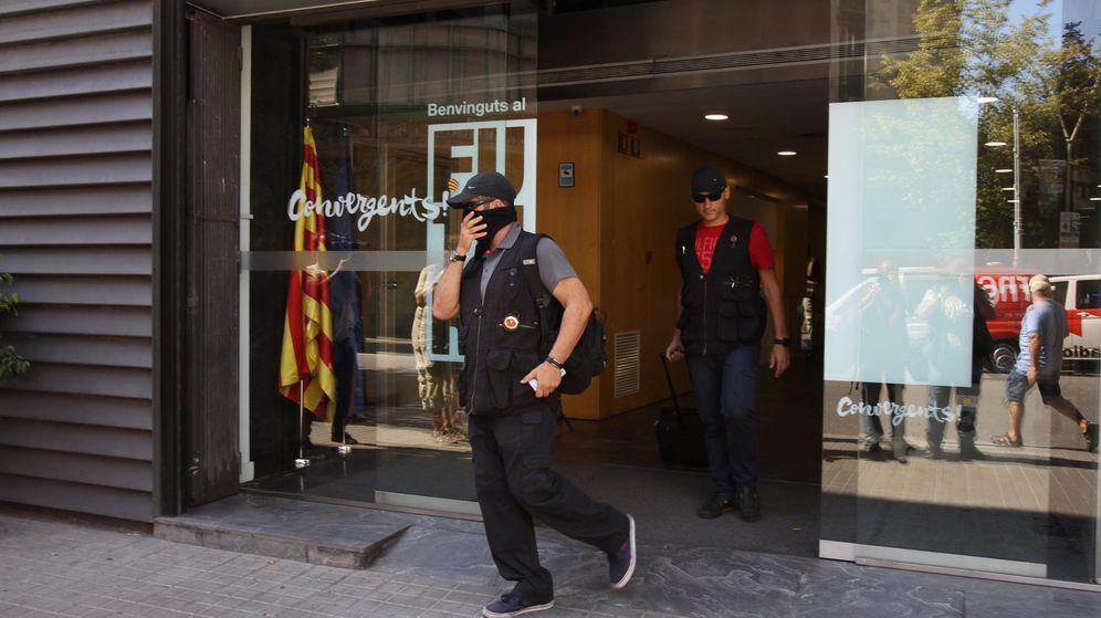 Foto: Efectivos de la Guardia Civil salen de la sede de CDC en la calle Córcega. (EFE)