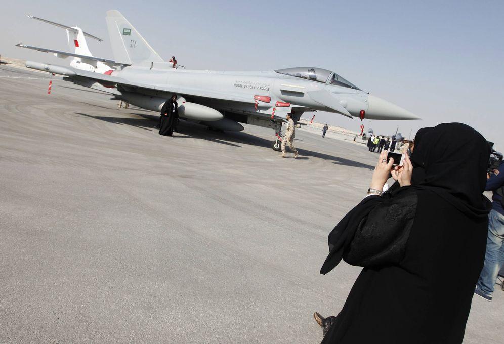 Foto: Una mujer fotografía a su amiga delante de un caza saudí durante una exhibición aérea en la base de Sakir, en Bahréin. (Reuters)