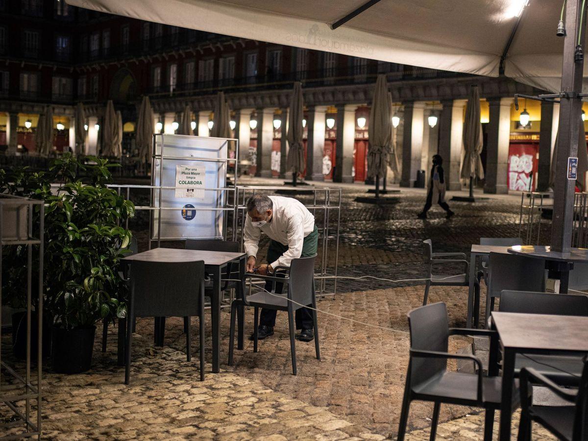 Foto: Un hombre, junto a una terraza de restauración vacía. (EFE)