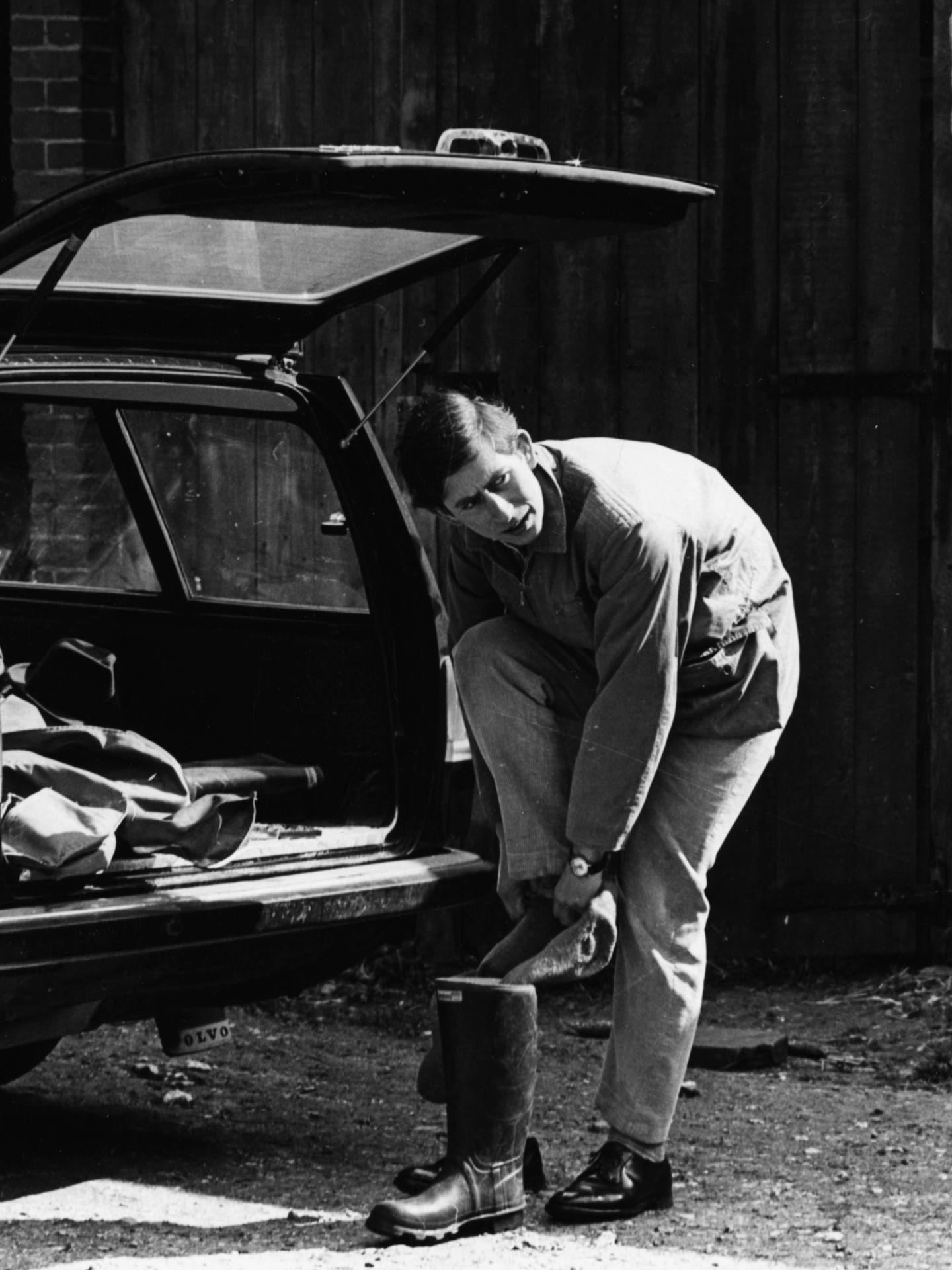 El príncipe Carlos poniéndose sus botas Wellington en abril de 1969. (Getty)