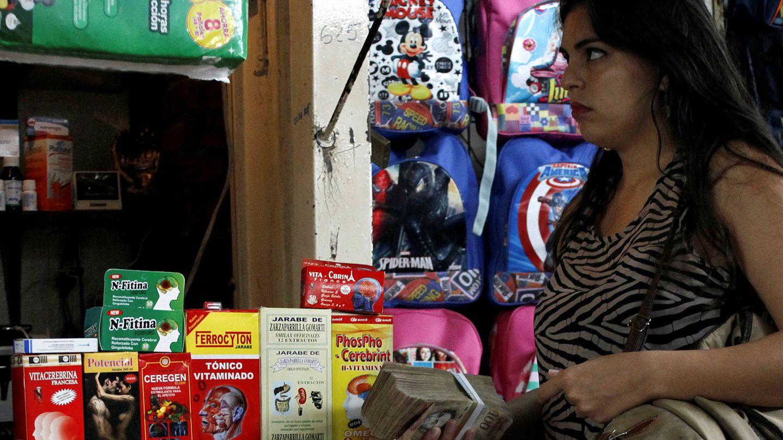 Una mujer sostiene un fajo de bolívares en un mercado en Rubio, Venezuela. (Reuters)