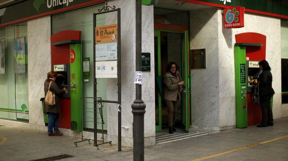 Foto: Unas mujeres sacan dinero de un cajero automático de Unicaja. (Reuters)
