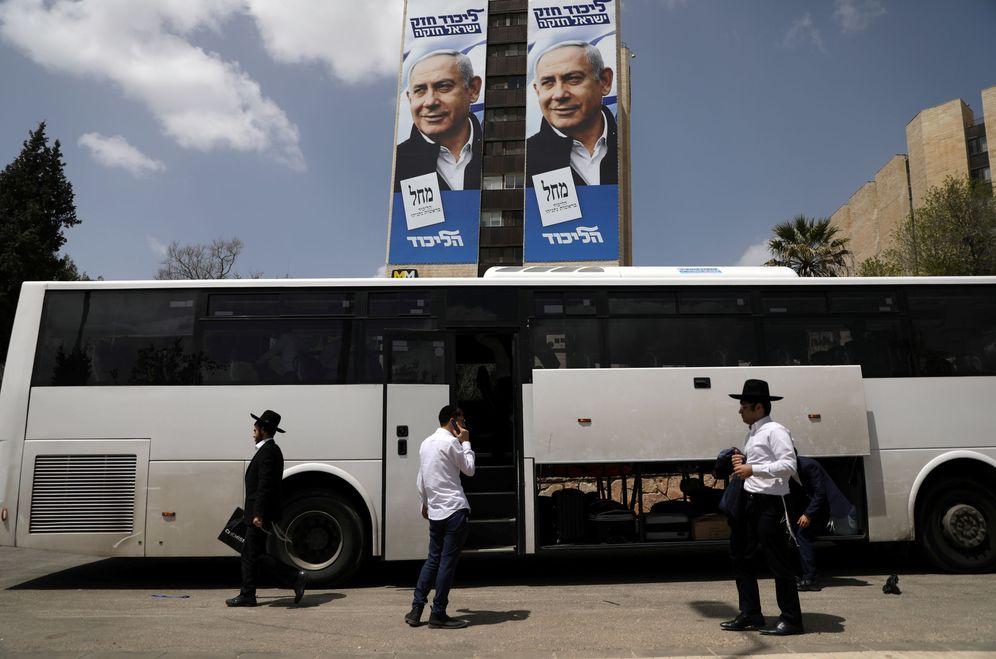Foto: Varios ultraortodoxos junto a un autobús y bajo un póster electoral de Netanyahu. (Reuters)