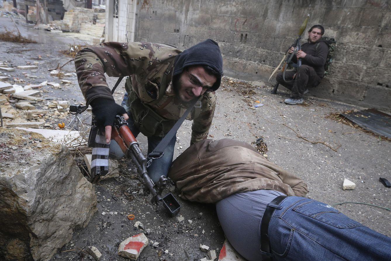 Foto: Un combatiente del Ejército Libre Sirio (ELS) ayuda a un compañero herido durante combates en Alepo, en el norte de Siria (Reuters).
