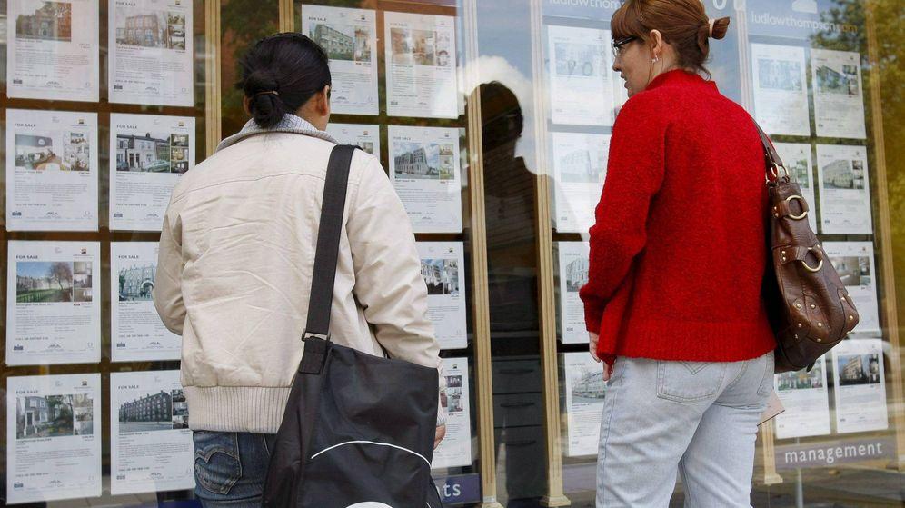 Foto: Dos jóvenes miran los carteles de viviendas en venta de una inmobiliaria. (EFE)