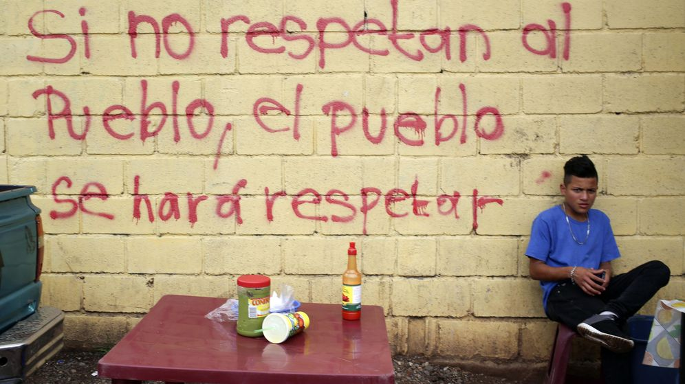 Foto: Un joven vende comida frente a un grafiti en una pared exterior de la sede del Tribunal Supremo Electoral de Tegucigalpa (Honduras). (EFE)