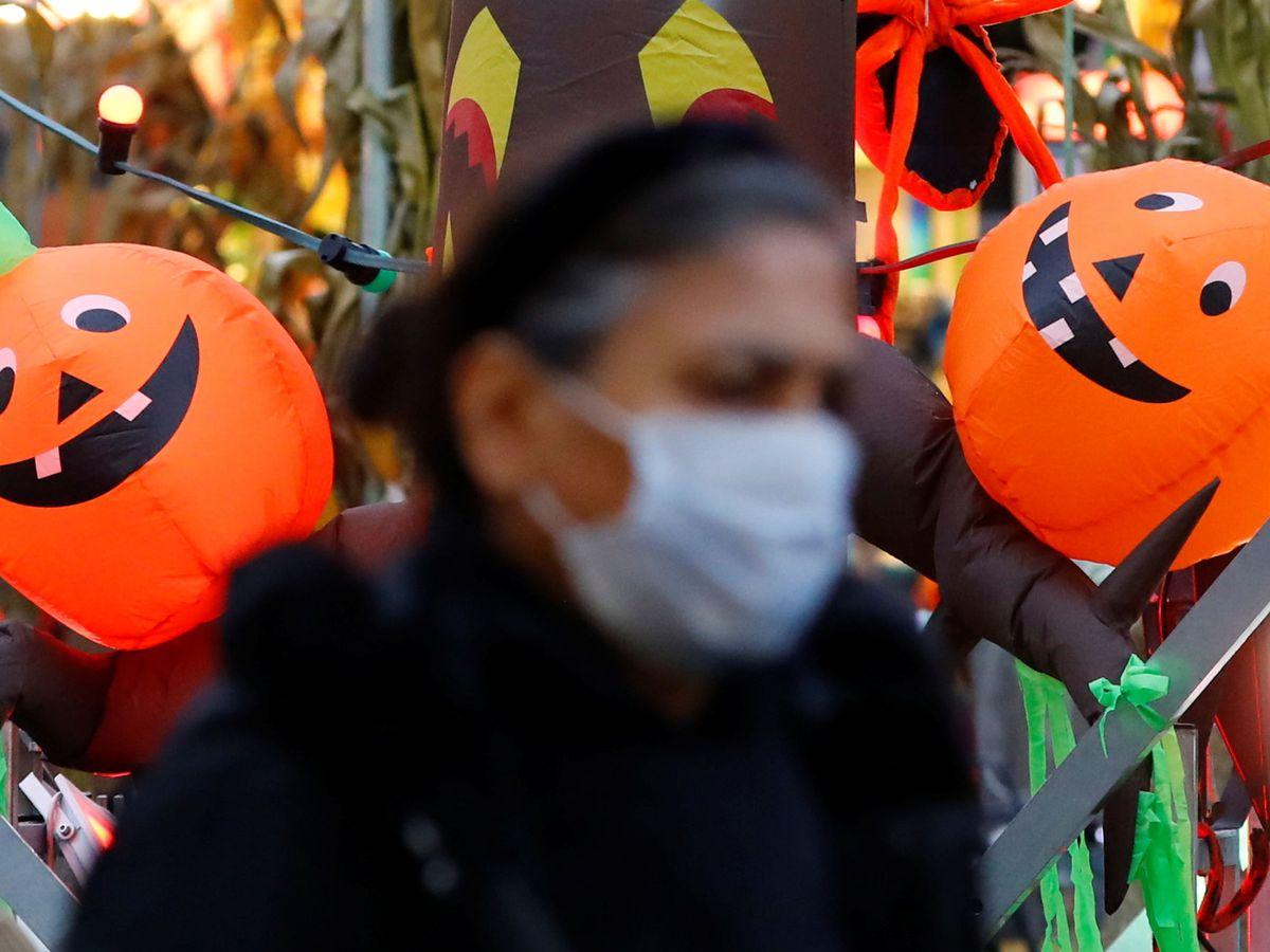 Foto: Mujer con mascarilla con calabazas de Halloween al fondo.