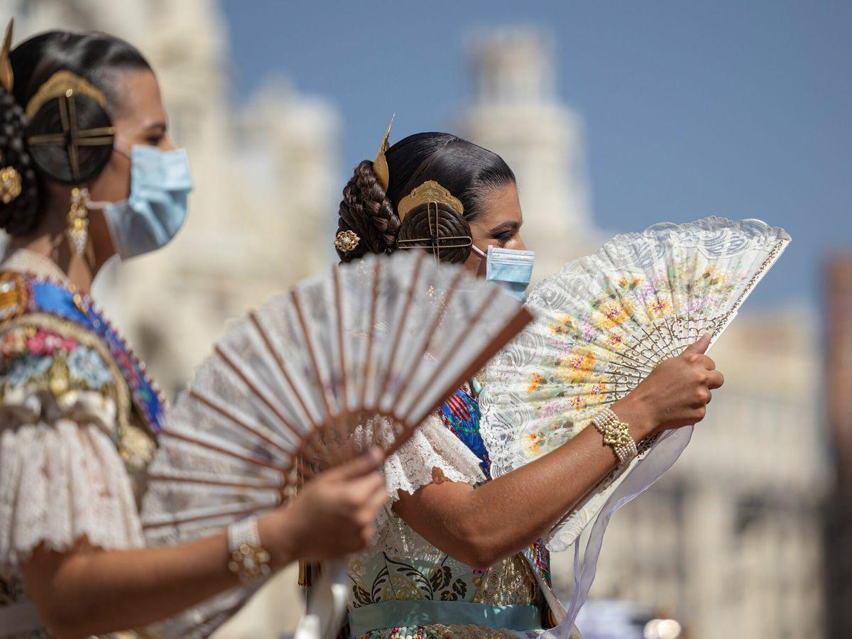 Foto: Dos falleras combaten el calor con abanicos. (EFE)