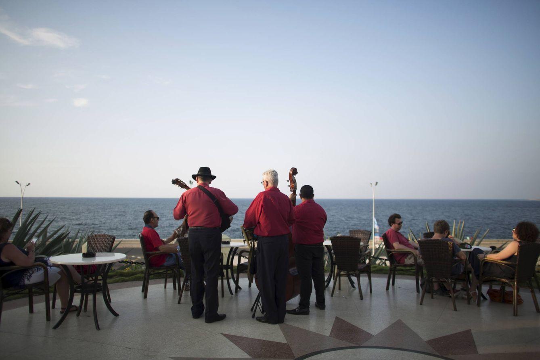 Foto: Músicos cubanos tocan canciones tradicionales mientras unos turistas disfrutan del atardecer en un hotel de La Habana. (Reuters)