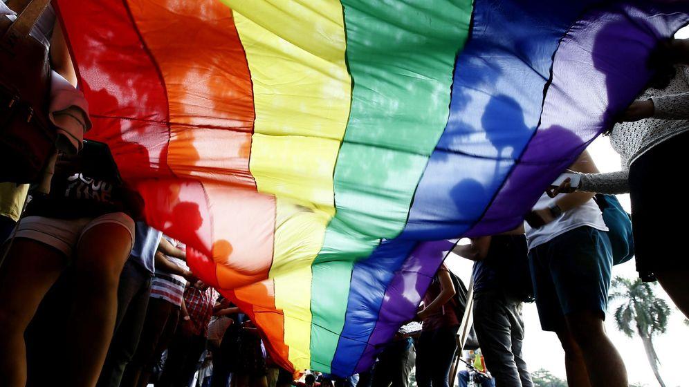 Foto: Activistas estudiantiles sujetan una bandera con el arcoiris durante una marcha del Oregullo. (Efe)