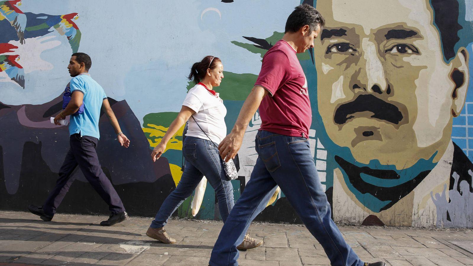 Foto: Varias personas pasan por delante de un mural con la cara del presidente Nicolás Maduro en Caracas, en 2015. (Reuters)