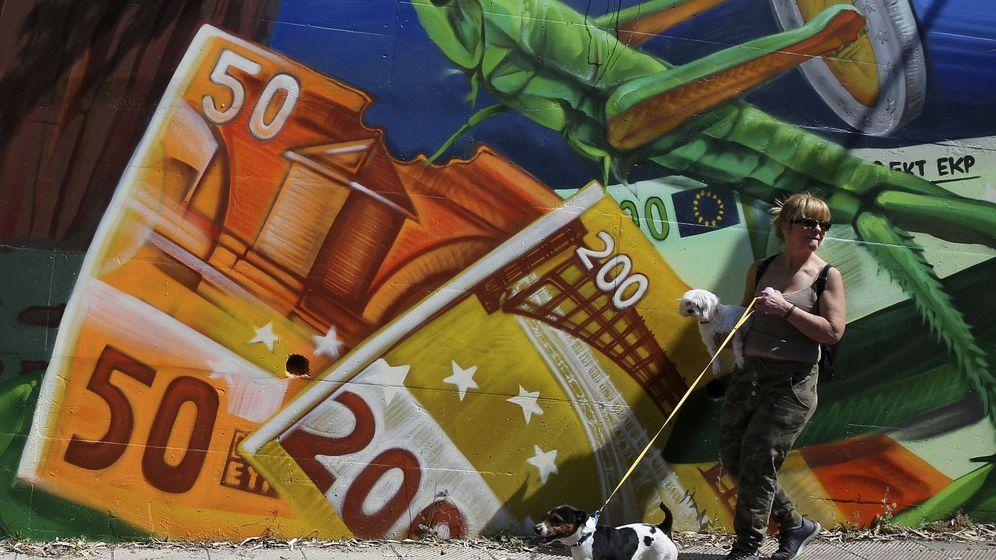 Foto: Una mujer pasa junto a una pintada de billetes de euro. (EFE)