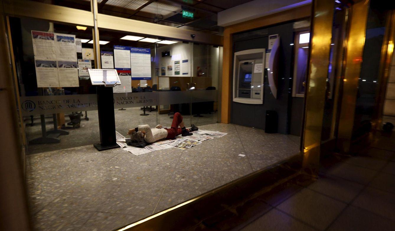 Foto: Un argentino duerme junto a un cajero de Banco de la Nación, junto al hotel donde Scioli y Kirchner ofrecían un acto de campaña en Buenos Aires