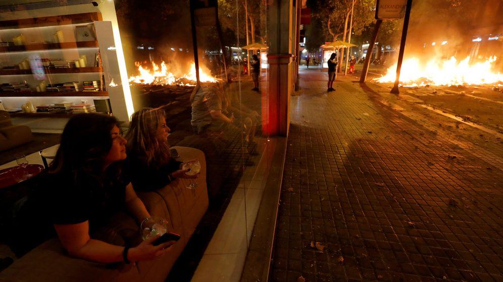 Foto: Dos mujeres son testigos de los disturbios en Barcelona desde un bar (REUTERS/Juan Medina)