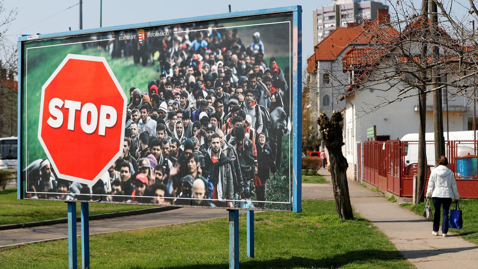 Foto: Una mujer pasa frente a un mural antiinmigración colocado por el partido gubernamental Fidesz, en Gyongyos, en abril de 2018. (Reuters)