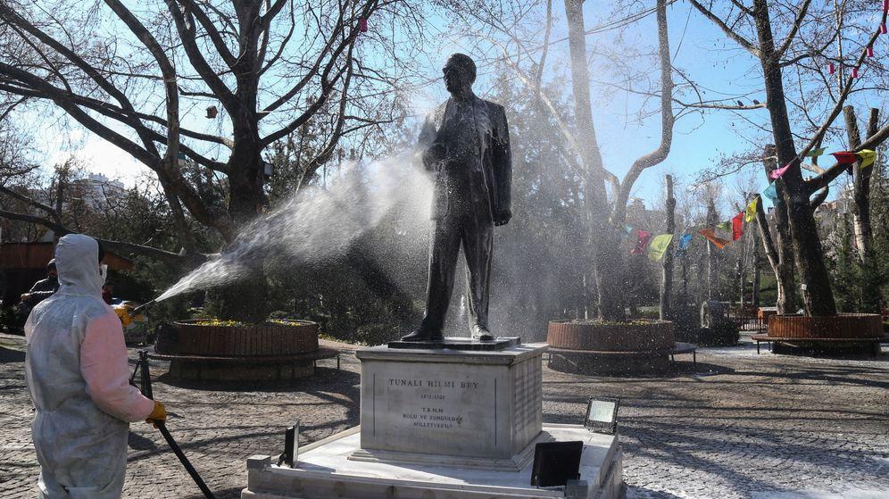Foto: Un operario de limpieza desinfecta la estatua de Tunali Hilmi, político turco, el pasado 17 de marzo. (EFE)