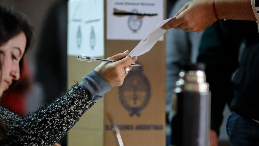 Foto: Un hombre recibe su papeleta electoral este domingo en Buenos Aires (Argentina). (EFE)