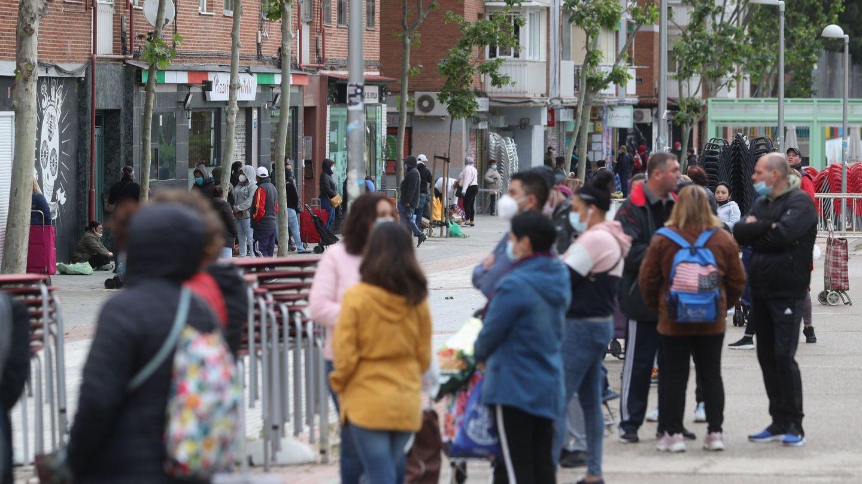 Numerosas personas esperan en fila para recoger alimentos proporcionados por la Asociación de vecinos de Aluche. Foto: Efe