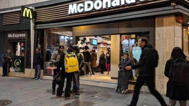 Foto:  Varios 'glovers' hablan en la puerta del McDonald´s de Cuatro Caminos. (M.MC)
