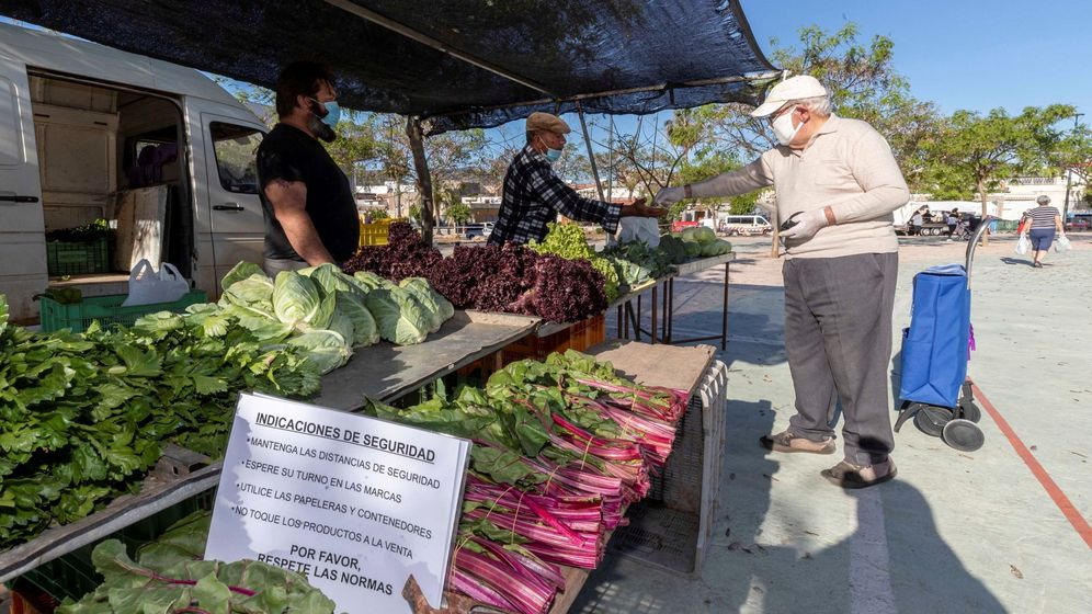 Foto: Un hombre paga la compra en un puesto de verduras del mercadillo semanal del Barrio Peral de Cartagena, el pasado día 11. (EFE)