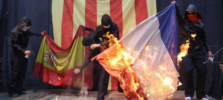 Foto: Encapuchados queman las banderas de España y Francia al acabar una manifestación independentista. (EFE)