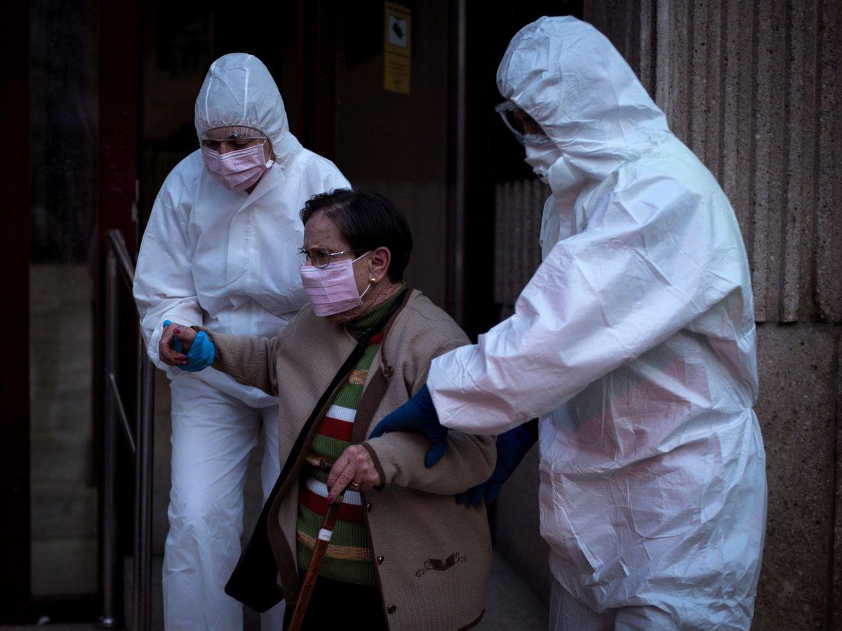 Foto: Dos trabajadores sanitarios trasladan a una anciana. (EFE)