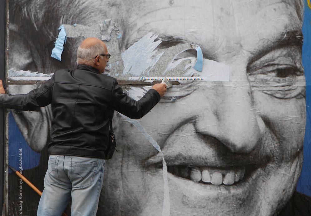 Foto: Un activista de un partido opositor húngaro retira un póster con la cara de George Soros, en Budapest. (Reuters)